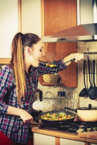 Woman in kitchen cooking stir fry frozen vegetables and tasting. Girl frying making delicious risotto. Dinner food meal.