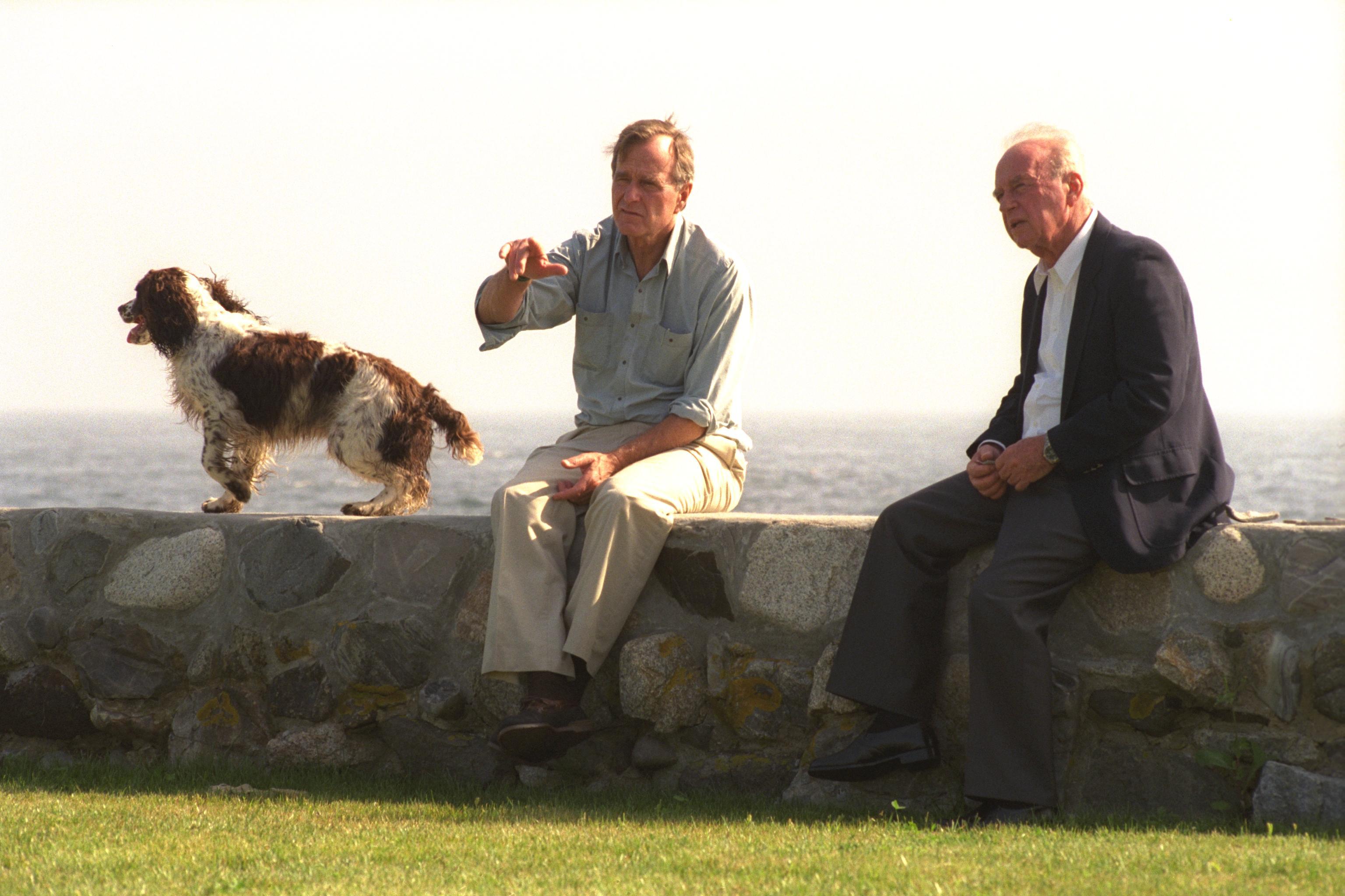 """TALKS BETWEEN P.M. YITZHAK RABIN AND U.S. PRES. GEORGE BUSH, SITTING ON A WALL, TO THE LEFT THE PRES.'S DOG, MILLIE. áé÷åø øàù äîîùìä éöç÷ øáéï áàøä""""á. áöéìåí, ùéçä áéï øä""""î éöç÷ øáéï ìðùéà àøä""""á â'åøâ' áåù, ëùäí éùåáéí òì âãø àáï ìùôú äàå÷éàðåñ, áçååúå äôøèéú ùì äðùéà á÷ðéáð÷ôåøè, áîãéðú """"îééï"""", àøä""""á."""