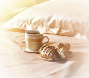 Cup with coffee, hot chocolate, cappuccino, latte or mochaccino and croissant on a bed