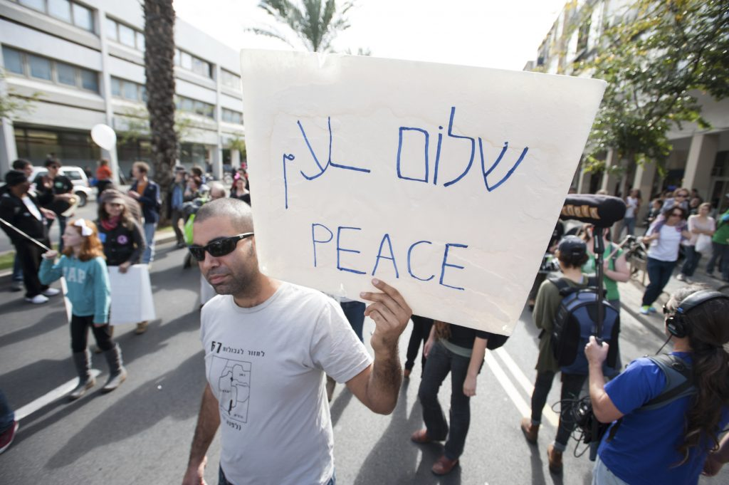 "Tel Aviv, Israel - December 7, 2012: An activist holds a sign reading ""Peace"" in Hebrew, Arabic, and English during the annual human rights march in Tel Aviv, Israel."