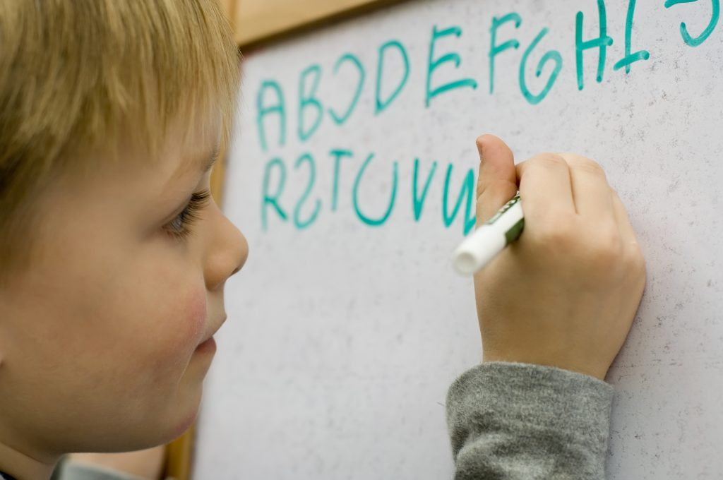 Little boy learning to write alphabet on white board