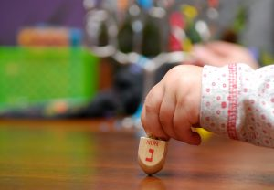 Hand of little girl spinning dreidel during Hanukkah celebration