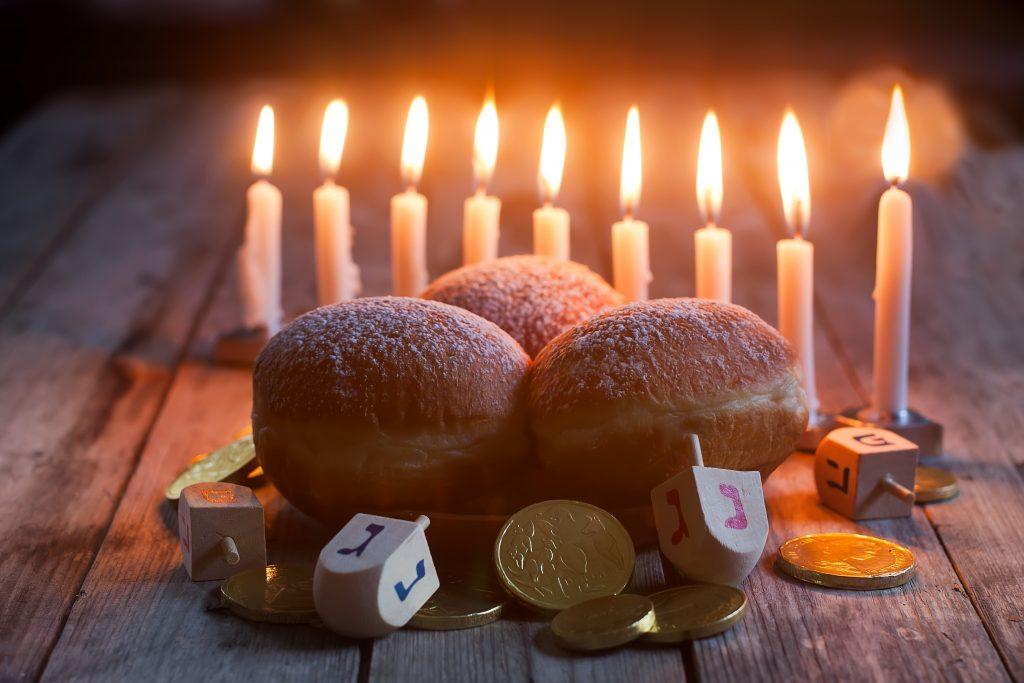Jewish holiday hannukah symbols - menorah, doughnuts, chockolate coins and wooden dreidels.