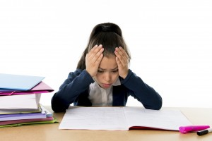 sweet little female latin child studying on desk looking bored and under stress with a tired face expression in children education and back to school concept isolated on white background