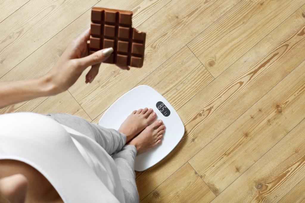 Diet. Young Woman Standing On Weighing Scale And Holding Chocolate Bar. Sweets Are Unhealthy Junk Food. Sugar Is Bad For Health. Dieting, Healthy Eating, Lifestyle. Weight Loss. Top View